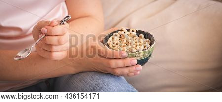 A Young Woman In Jeans And A Pink T-shirt Is Holding A Beautiful Spoon And A Bowl Of Organic Yogurt