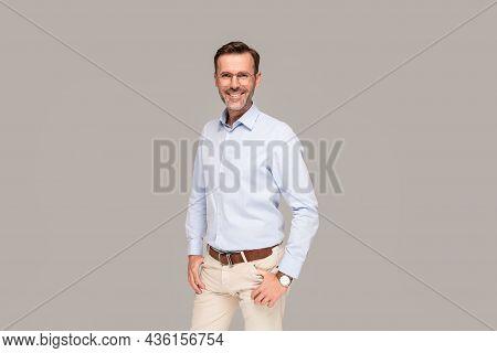 Portrait Of Handsome Elegant Man Looking At The Camera. Studio Shot. Gray Studio Background. A Lot O