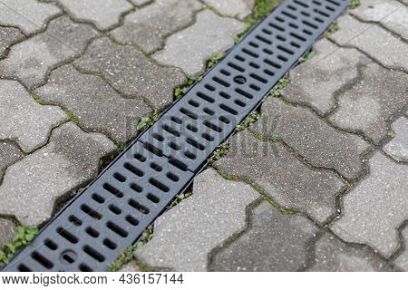 Grating Of Drainage System Rainwater In The Park At The Sidewalk From A Stone Shaped Paving Slabs. L