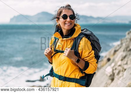 A Young Woman In Tourist Gear Stands Against The Background Of The Sea And Looks Into The Camera. A