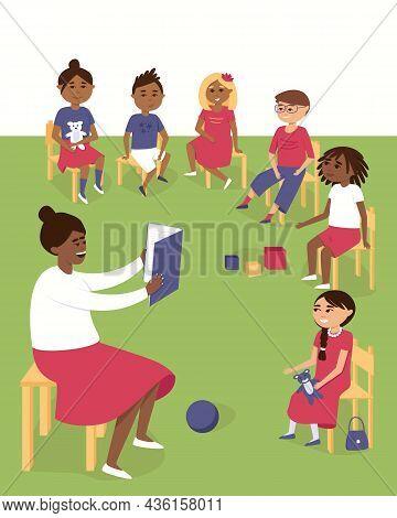 The Teacher Reads A Book To Children In Kindergarten. African American, Asian And European Children