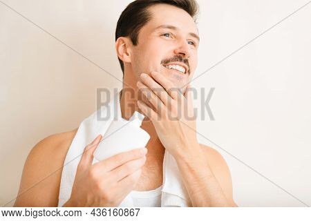Charming Happy Young Man With Towel On Shoulders Applying Moisturizing After Shave Lotion, Handsome