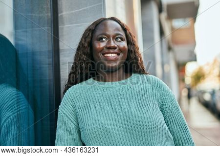 Young african woman smiling happy leaning on the wall