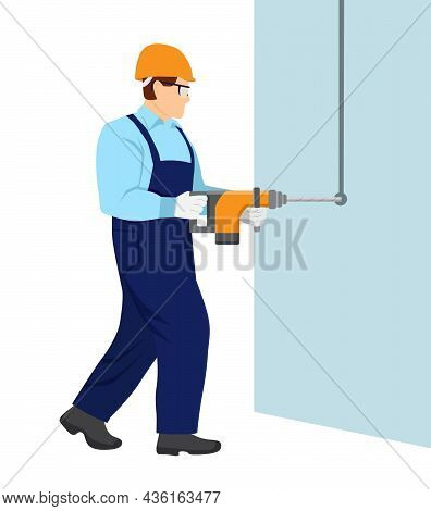 A Man In Overalls And With A Helmet On His Head Is Working With A Hammer Drill. Guy Drills A Hole In