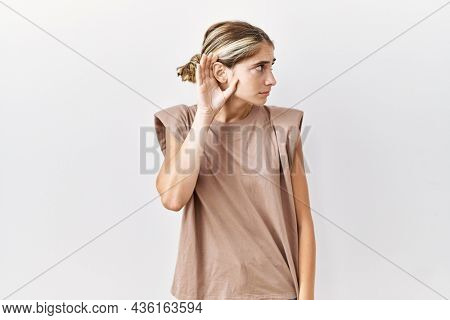 Young blonde woman standing over isolated background smiling with hand over ear listening an hearing to rumor or gossip. deafness concept.