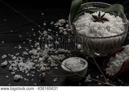 The Salt Crystals On Black Stone Plate Background. Healthy Sea Salt. Vintag Style, Selective Focus.