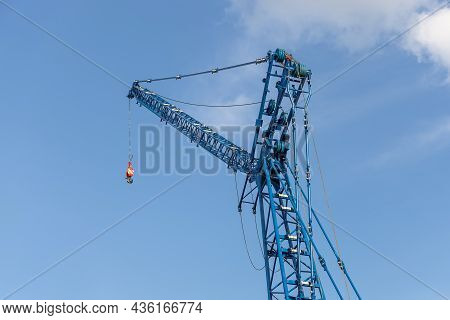 Lattice Jib Of A Crawler Crane Against The Blue Sky, Low Viewing Angle. Heavy Equipment For Construc
