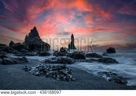 Beach Section In The South Of Iceland In The Evening At Sunset. Black Sand With Rock Needle And Ston