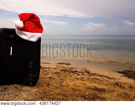 A Santa Claus Hat Is Hanging On A Black Suitcase. Christmas On The Beach. Winter Travel