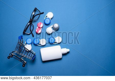 Contact Lenses, Eye Glasses And Eye Solution Bottle In The Shopping Cart On The Blue Flat Lay Backgr