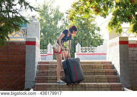 A Woman With A Heavy Suitcase Hardly Climbs The Stairs Of The Railway Station.
