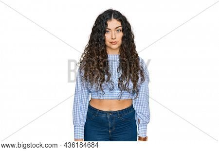 Young hispanic girl wearing casual clothes relaxed with serious expression on face. simple and natural looking at the camera.
