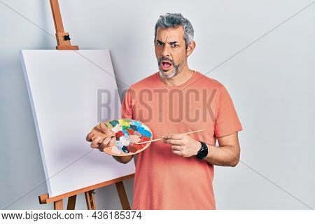 Handsome middle age man with grey hair standing drawing with palette by painter easel stand in shock face, looking skeptical and sarcastic, surprised with open mouth