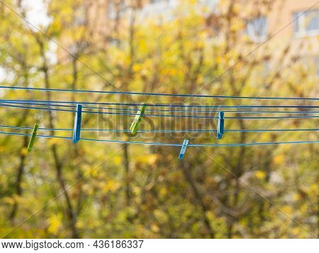 Plastic Clothes Pins Blue And Green Hanging On Blue Clothesline
