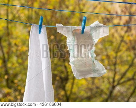 Baby Diapers Hanging On A Clothesline, Paper Diaper And Cotton Diaper With Clothes Pin