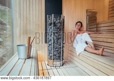 Relaxing Woman Wrapped White Towel Sitting On The Wooden Bench In Hot Finnish Sauna With A Huge Wide