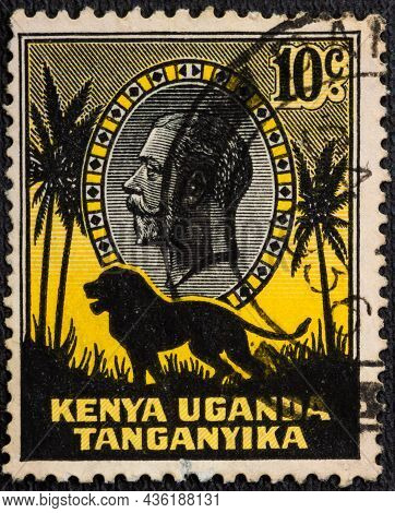 : A Stamp Printed In East Africa Showing Image Of A Lion And Palm Trees Against The Portrait Of King