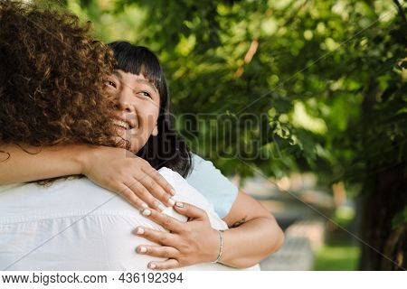 Happy young multiethnic couple cuddling embracing together in the green park close up