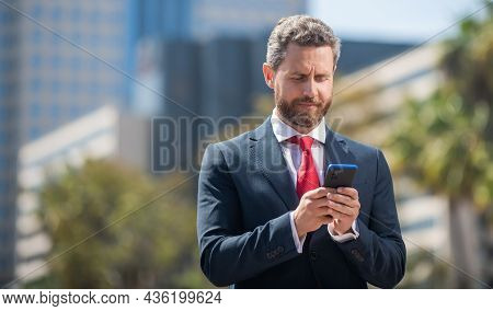Bearded Businessperson In Formalwear Chating On Smartphone Outside The Office, Communication