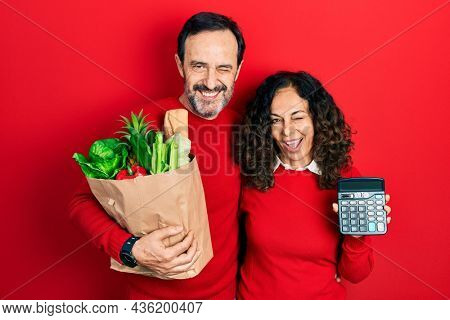 Middle age couple of hispanic woman and man holding groceries bag and calculator winking looking at the camera with sexy expression, cheerful and happy face.