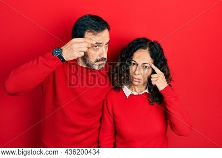 Middle age couple of hispanic woman and man hugging and standing together pointing unhappy to pimple on forehead, ugly infection of blackhead. acne and skin problem
