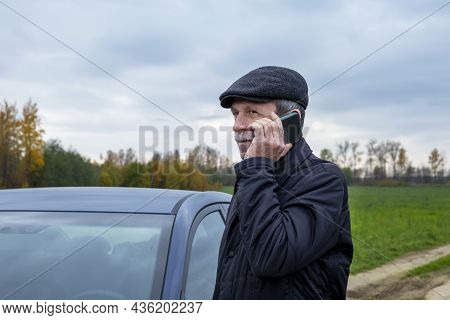 Adult Pensioner Gets Into Car And Talks On Smartphone Against Backdrop Of Rural Landscape In Autumn.