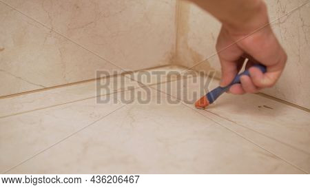 Laying Floor Tiles, Tiler Cleaning Tiles After Filling Up Joints. New Floor Tiles. Cleaning Tile Joi