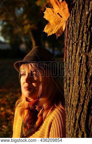 Close-up Portrait Of Pretty Caucasian Blonde Woman In Colorful Orange Autumn Park. Bright Stylish Wo