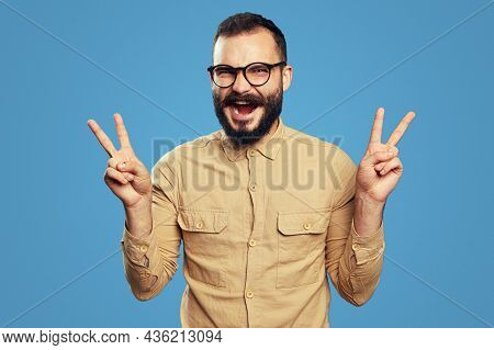 Optimistic Unshaven Man Screams And Shows V Sign Or Victory Gesture With Both Hands, Wears Eyeglasse