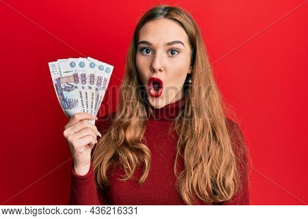 Young blonde woman holding russian 500 ruble banknotes scared and amazed with open mouth for surprise, disbelief face