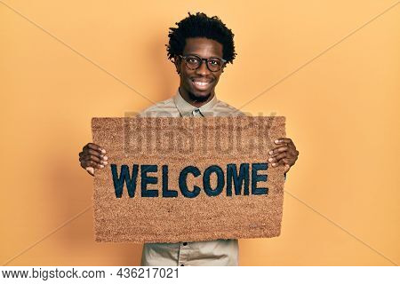 Young african american man holding welcome doormat smiling with a happy and cool smile on face. showing teeth.