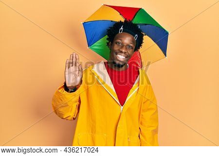 Young african american man wearing yellow raincoat waiving saying hello happy and smiling, friendly welcome gesture