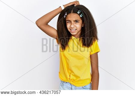 Young african american girl standing over white isolated background confuse and wonder about question. uncertain with doubt, thinking with hand on head. pensive concept.
