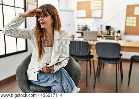 Hispanic business woman working at the office very happy and smiling looking far away with hand over head. searching concept.