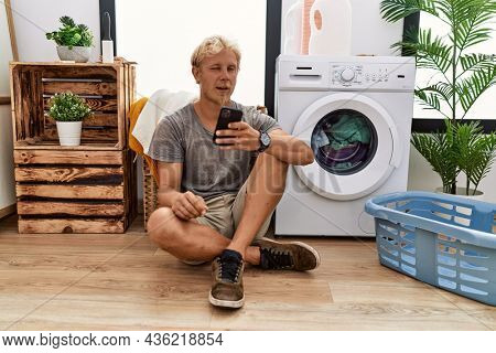 Young blond man doing laundry using smartphone winking looking at the camera with sexy expression, cheerful and happy face.