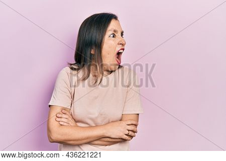 Middle age hispanic woman with arms crossed gesture angry and mad screaming frustrated and furious, shouting with anger. rage and aggressive concept.