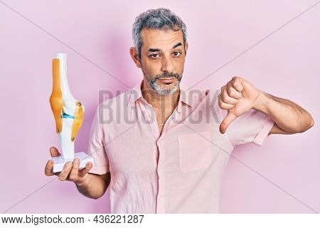 Handsome middle age man with grey hair holding anatomical model of knee joint with angry face, negative sign showing dislike with thumbs down, rejection concept