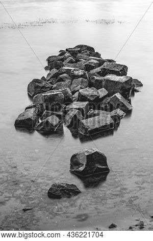 Pile Of Heavy Basalt Blocks In The Water Of A Dutch River