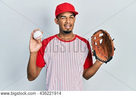 Young african american man wearing baseball uniform holding glove and ball winking looking at the camera with sexy expression, cheerful and happy face.