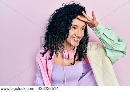 Young hispanic woman with curly hair wearing gym clothes and using headphones very happy and smiling looking far away with hand over head. searching concept.