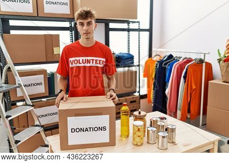 Young caucasian man volunteer holding donations box relaxed with serious expression on face. simple and natural looking at the camera.
