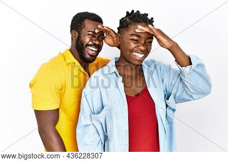 Young african american couple wearing casual clothes very happy and smiling looking far away with hand over head. searching concept.