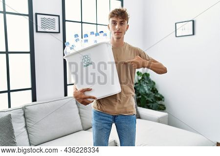 Young caucasian man holding wastebasket with recycling plastic bottles at home pointing finger to one self smiling happy and proud