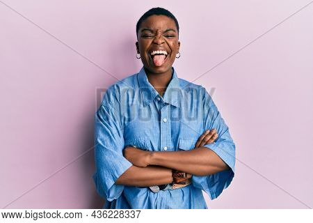 Young african american woman with arms crossed gesture sticking tongue out happy with funny expression.