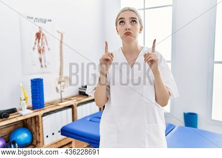 Young caucasian woman working at pain recovery clinic pointing up looking sad and upset, indicating direction with fingers, unhappy and depressed.