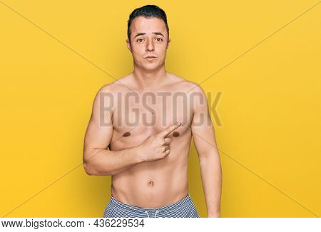 Handsome young man wearing swimwear shirtless pointing aside worried and nervous with forefinger, concerned and surprised expression