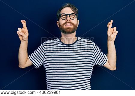 Caucasian man with beard wearing striped t shirt and glasses gesturing finger crossed smiling with hope and eyes closed. luck and superstitious concept.