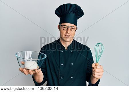 Handsome young man holding bread dough and blender in shock face, looking skeptical and sarcastic, surprised with open mouth