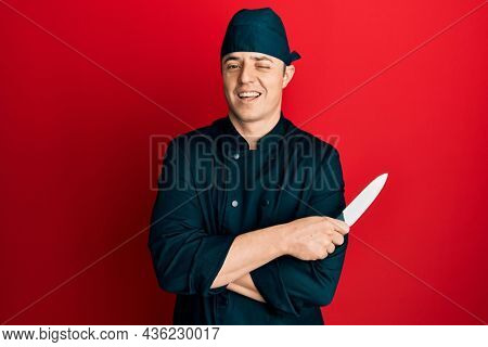 Handsome young man wearing professional cook uniform holding knife winking looking at the camera with sexy expression, cheerful and happy face.