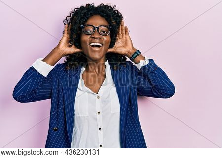 Young african american woman wearing business clothes and glasses smiling cheerful playing peek a boo with hands showing face. surprised and exited